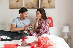 Jeunes couples mignons donnant un lapin comme cadeau images stock