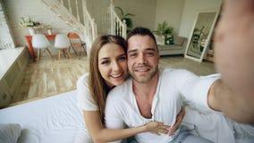 Jeunes couples mignons et affectueux ayant la causerie visuelle tenant la tablette et causant aux parents s'asseyant dans le lit  Photographie stock