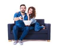 Jeunes couples mignons heureux se reposant sur le sofa avec le maïs éclaté et le watchin Photographie stock