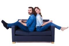 Jeunes couples mignons heureux se reposant sur le sofa d'isolement sur le blanc Image libre de droits