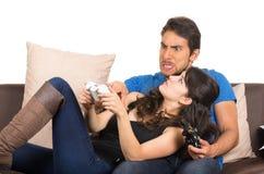 Jeunes couples mignons jouant des jeux vidéo Image stock