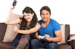 Jeunes couples mignons jouant des jeux vidéo Photographie stock libre de droits