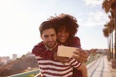 Jeunes couples mignons prenant les selfies espiègles Photo stock