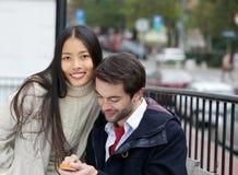 Jeunes couples mignons regardant le téléphone portable ensemble Photos stock