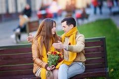Jeunes couples mignons se reposant dans le banc de parc et parlant pendant la date Photos libres de droits