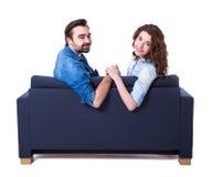 Jeunes couples mignons se reposant sur le sofa d'isolement sur le blanc Images libres de droits