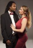 Jeunes couples mélangés mignons contre le noir Images stock