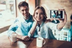 Jeunes couples modernes prenant des photos de lui-même au téléphone, se reposant à la table en café Images libres de droits