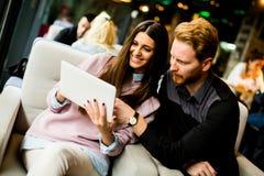 Jeunes couples modernes se reposant ensemble et à l'aide d'un comprimé Photo stock