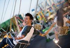 Jeunes couples montant les oscillations à un parc d'attractions Images libres de droits