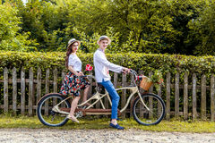 Jeunes couples montant un tandem de vélo en parc Photos stock