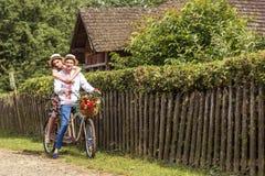 Jeunes couples montant un tandem de vélo en parc Photo stock