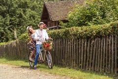 Jeunes couples montant un tandem de vélo en parc Image stock