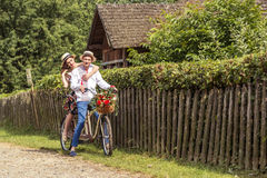 Jeunes couples montant un tandem de vélo en parc Photographie stock