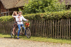 Jeunes couples montant un tandem de vélo en parc Photo libre de droits