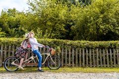 Jeunes couples montant un tandem de vélo en parc Dans la perspective de la barrière de l'arbre Photos libres de droits