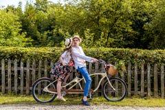 Jeunes couples montant un tandem de vélo en parc Dans la perspective de la barrière de l'arbre Photographie stock libre de droits