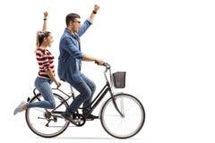 Jeunes couples montant une bicyclette et faisant des gestes le bonheur photo stock