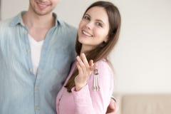 Jeunes couples montrant les clés de nouvelle maison, propriétaires avec des clés Images libres de droits