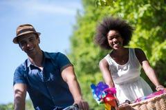 Jeunes couples multi-ethniques ayant un tour de vélo en nature Image stock