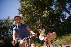 Jeunes couples multi-ethniques ayant un tour de vélo en nature Photographie stock libre de droits