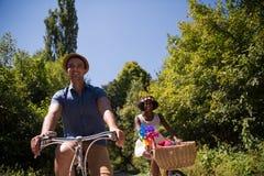 Jeunes couples multi-ethniques ayant un tour de vélo en nature Image libre de droits