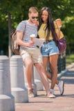 Jeunes couples multi-ethniques des touristes avec des tasses de carte et de café dans la ville Images libres de droits