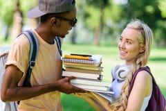 Jeunes couples multi-ethniques heureux tenant des livres ensemble tout en se tenant en parc Images libres de droits
