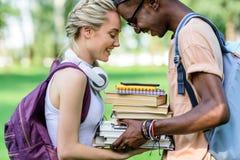 Jeunes couples multi-ethniques heureux tenant des livres ensemble tout en se tenant en parc Image libre de droits