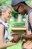 Jeunes couples multi-ethniques heureux tenant des livres ensemble tout en se tenant en parc Images stock