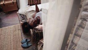 Jeunes couples multiraciaux dans des pyjamas se trouvant sur le lit et la musique de écoute Smartphone d'utilisation d'homme et d banque de vidéos