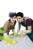 Jeunes couples nettoyant une table Photographie stock libre de droits