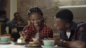 Jeunes couples noirs attrayants dans un cafétéria Photos stock