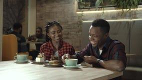 Jeunes couples noirs attrayants dans un cafétéria Photographie stock libre de droits