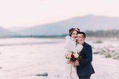 Jeunes couples nuptiales attrayants posant sur Pebble Beach près de la rivière de montagne Photos libres de droits