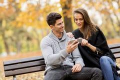 Jeunes couples observant heureusement quelque chose sur un smartphone et un sitt image stock