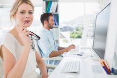 Jeunes couples occasionnels de sourire travaillant sur des ordinateurs Photo libre de droits