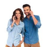 Jeunes couples occasionnels heureux parlant à leurs téléphones Photos stock