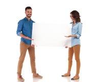 Jeunes couples occasionnels heureux présentant le grand conseil vide Image stock