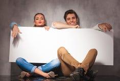 Jeunes couples occasionnels riant et montrant un grand panneau d'affichage vide Photos libres de droits