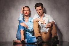 Jeunes couples occasionnels se reposant sur le plancher Photographie stock