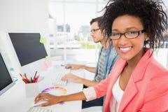 Jeunes couples occasionnels travaillant sur des ordinateurs Image stock