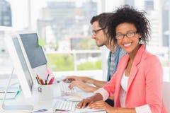 Jeunes couples occasionnels travaillant sur des ordinateurs dans le bureau Image libre de droits