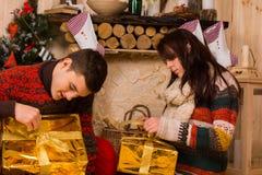 Jeunes couples ouvrant les cadeaux de fête de Noël d'or Photos libres de droits
