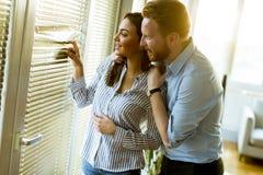 Jeunes couples par la fenêtre images stock