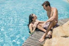 Jeunes couples par la piscine Image libre de droits
