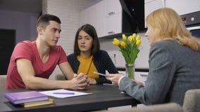 Jeunes couples parlant à l'agent au sujet de l'hypothèque banque de vidéos