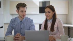 Jeunes couples parlant au-dessus de l'ordinateur portable pendant le petit déjeuner dans la cuisine banque de vidéos