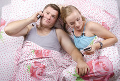Jeunes couples parlant au téléphone se situant dans le lit Image stock