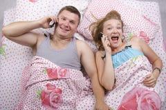 Jeunes couples parlant au téléphone se situant dans le lit Image libre de droits